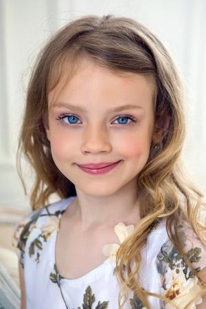 7 歳のブロンドの髪と白いドレスの少女の肖像画