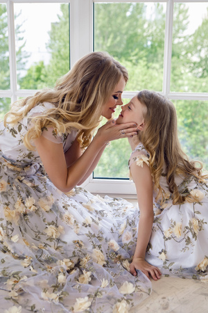 mother kissing daughter in matching dresses Stock Photo