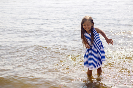 slow motion: baby girl in a striped dress and runs to the sea the ocean