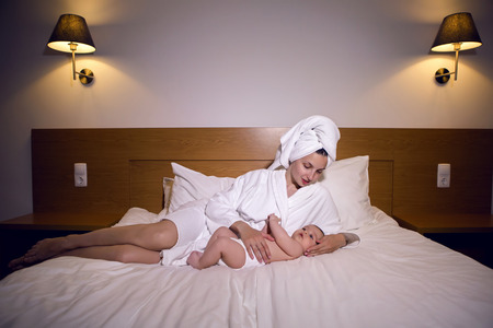 mother in a bathrobe lying on bed with son