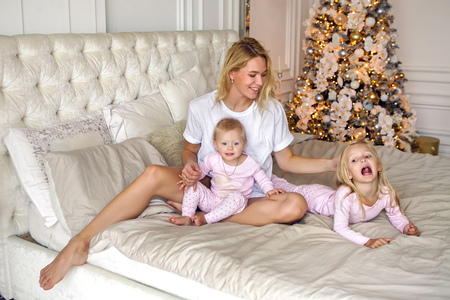 Mutter mit zwei Töchtern in ihren Pyjamas, die auf dem Bett im neuen Jahr sitzen Standard-Bild - 89762537