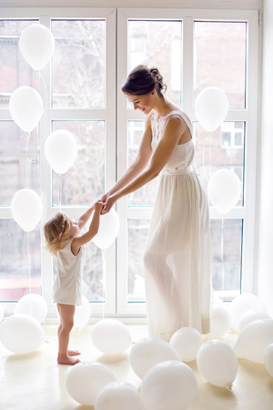 mother and daughter standing at the large window with the white balls in the Studio 写真素材