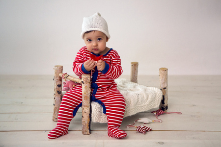 Child sits on a small wooden bed in red striped pajamas Stock Photo