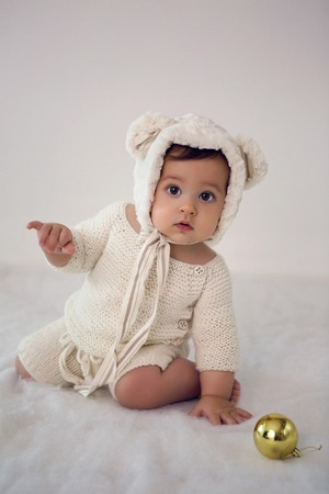 child of eight months sitting in the studio in a hat with bear ears