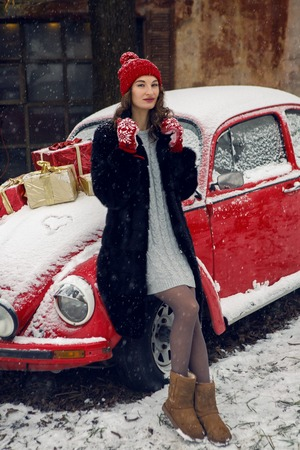 girl in red cap in winter is near red retro car beetle