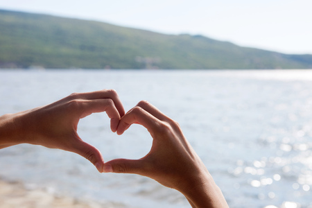 woman put her hands in the form of a heart against the sea