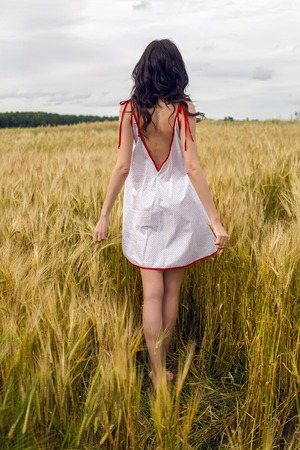 woman in a red light dress stands in a field with yellow dry ears of wheat in the summer