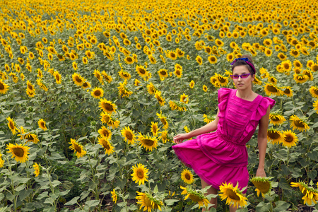 woman in a pink dress standing in the field with sunflowers in the summer