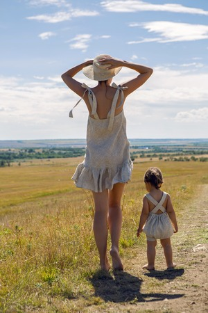 mother and son goes to the field at sunset in a straw hat