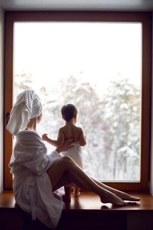 mom and son sitting by the window on a wide windowsill in a bathrobe after a bath