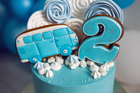blue cake on childrens birthday with the number two and a car on the background of balloons