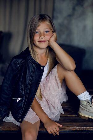 modisches Mädchenmodell in Lederjackenrock und Schuhen sitzt im Studio an der Wand