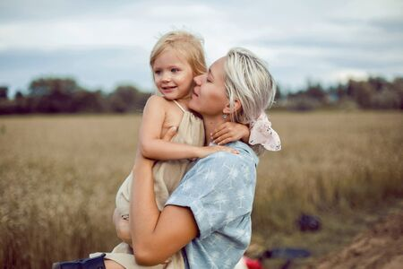 mom holds her daughter in the field with ears of wheat in the summer
