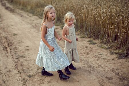 two girls in long dresses walk along the path to the field of dry wheat