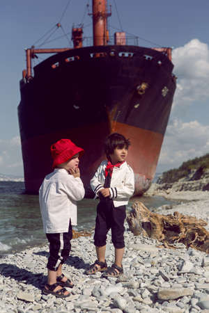 two fashionable baby boys stand next to a large Rio ship that ran aground off Novorossiysk