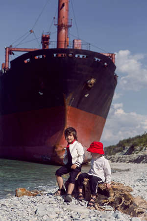 two fashionable baby boys sit next to a large Rio ship that ran aground off Novorossiysk 免版税图像