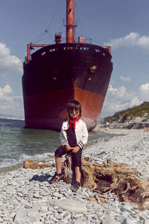 fashionable boy child with long hair sits on a log next to a large ship that ran aground near Novorossiysk