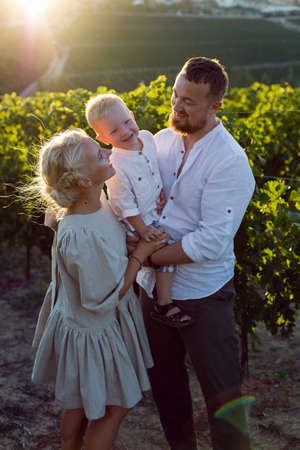 family of three in light clothes stand in a grape field during sunset in summer