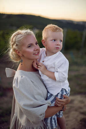 blonde woman in a dress holds her baby boy in her arms in a vineyard during sunset 版權商用圖片