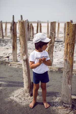 child boy in a cap t shirt and shorts holds a phone in his hands and stands on a pink lake among old logs