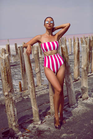 fashionable woman in a striped bathing suit stands next to logs on a pink lake wearing sunglasses