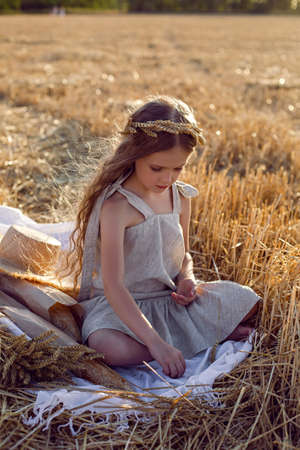 girl child in a dress and a wreath on her head sit on a mown field of wheat at sunset in summer