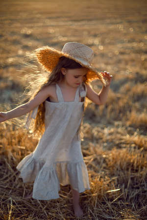girl child with long hair walking across the field wearing a hat with long hair during sunset
