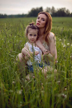 mom and daughter are sitting in a green field in white t-shirt