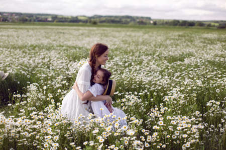 mother with daughter in a white dress and hat stand in a daisy field in summer