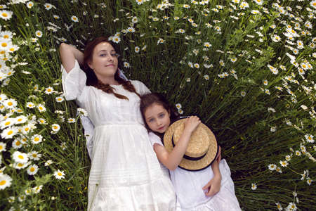 mother with daughter in a white dress lie on a camomile field 版權商用圖片