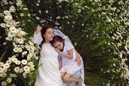mother with daughter in a white dress lie on a camomile field 免版税图像
