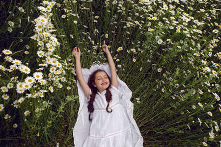 girl child lies on a camomile field in a white dress in summer 版權商用圖片