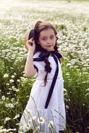portrait girl child in a white dress standing on a daisy field in a hat