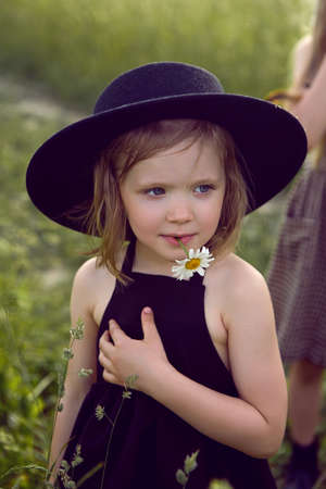 child girl in a black hat and dress stands in a field with a camomile in her mouth in summer 免版税图像