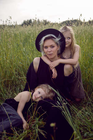 mother in an evening dress and a retro camera with two daughters on a green field with grass in the summer