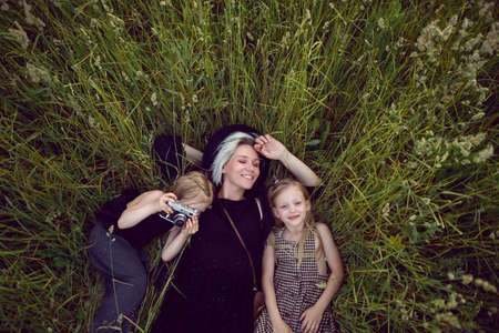 mother in an evening dress and a retro camera with two daughters is lying on a green field with grass in the summer
