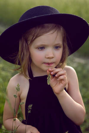child girl in a black hat and dress stands in a field with a grass in her mouth in summer 免版税图像
