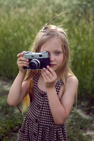 little girl child in a checkered dress stands with a retro camera and photographs in the summer field 免版税图像