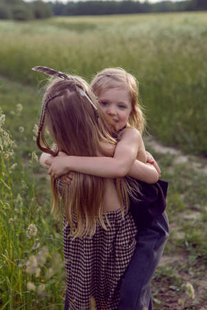 two sisters blondes in a field are played in indians in summer