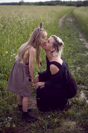 mom and daughter sit in the field in the summer and kiss