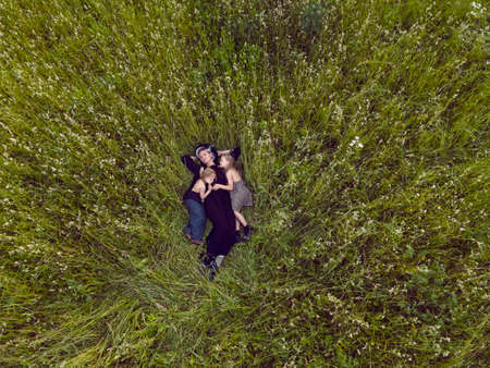 mother in an evening dress and a retro camera with two daughters is lying on a green field with grass in the summer Imagens