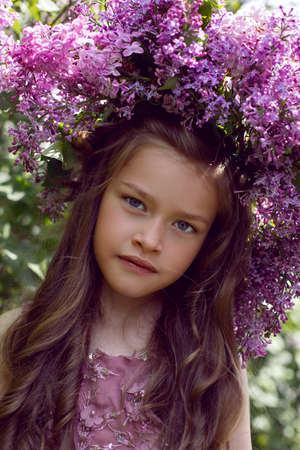 Caucasian girl child seven years old in a purple dress stands in nature with a wreath of lilacs