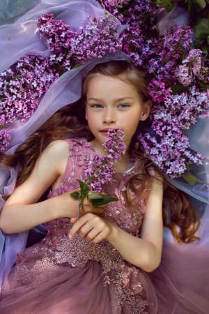 child girl in a purple floral dress lies on the ground among lilacs on a veil in spring 版權商用圖片
