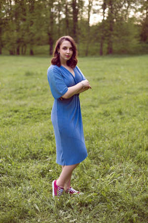 portrait of a girl standing on a green field in a blue dress