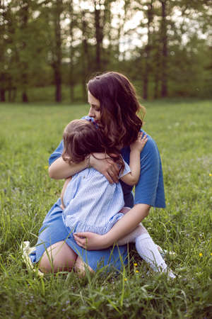 mom and daughter are sitting on a green meadow in blue dresses 免版税图像
