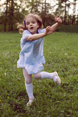 little beautiful girl of three years in a blue dress jumps on a green field