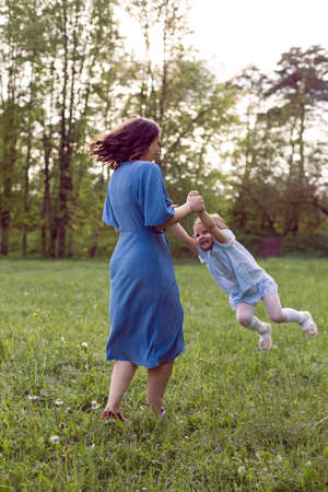 mother and daughter in a blue dress are played in the spring on a green field with dandelions