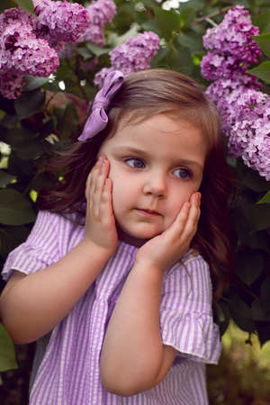 three-year-old girl stands in lilac bushes in a dress and a bow on her head