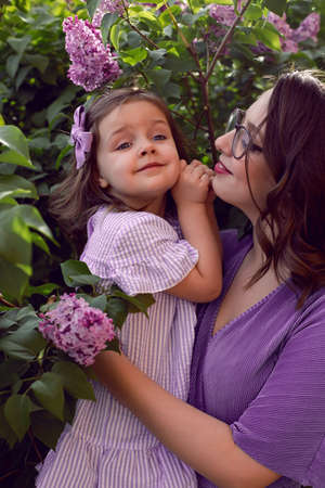 girl with mom in lilac dresses stand next to the lilac