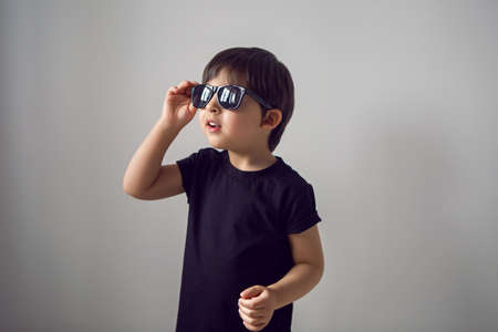 boy in a black t-shirt stands at home against the background of a white room in sunglasses ,during quarantine and thinks about traveling to countries Foto de archivo